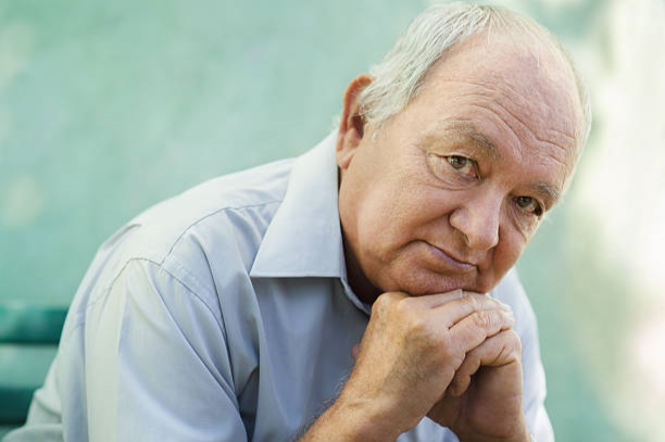Senior man's face leaning on hands