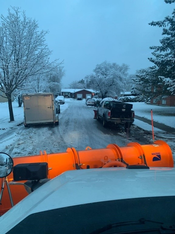 Snow plow on a street with cars parked