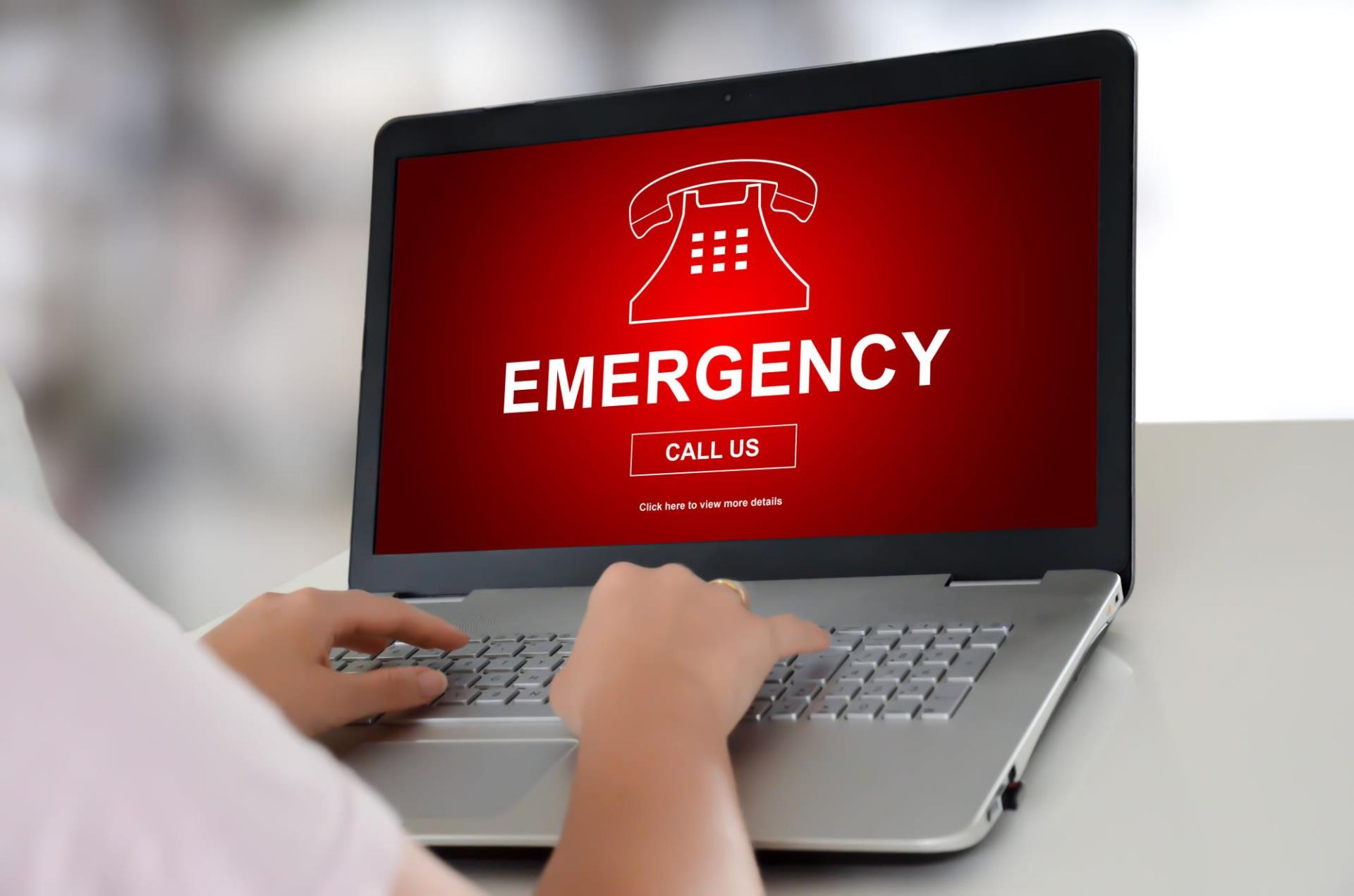 Hands typing on laptop with Emergency displayed on screen