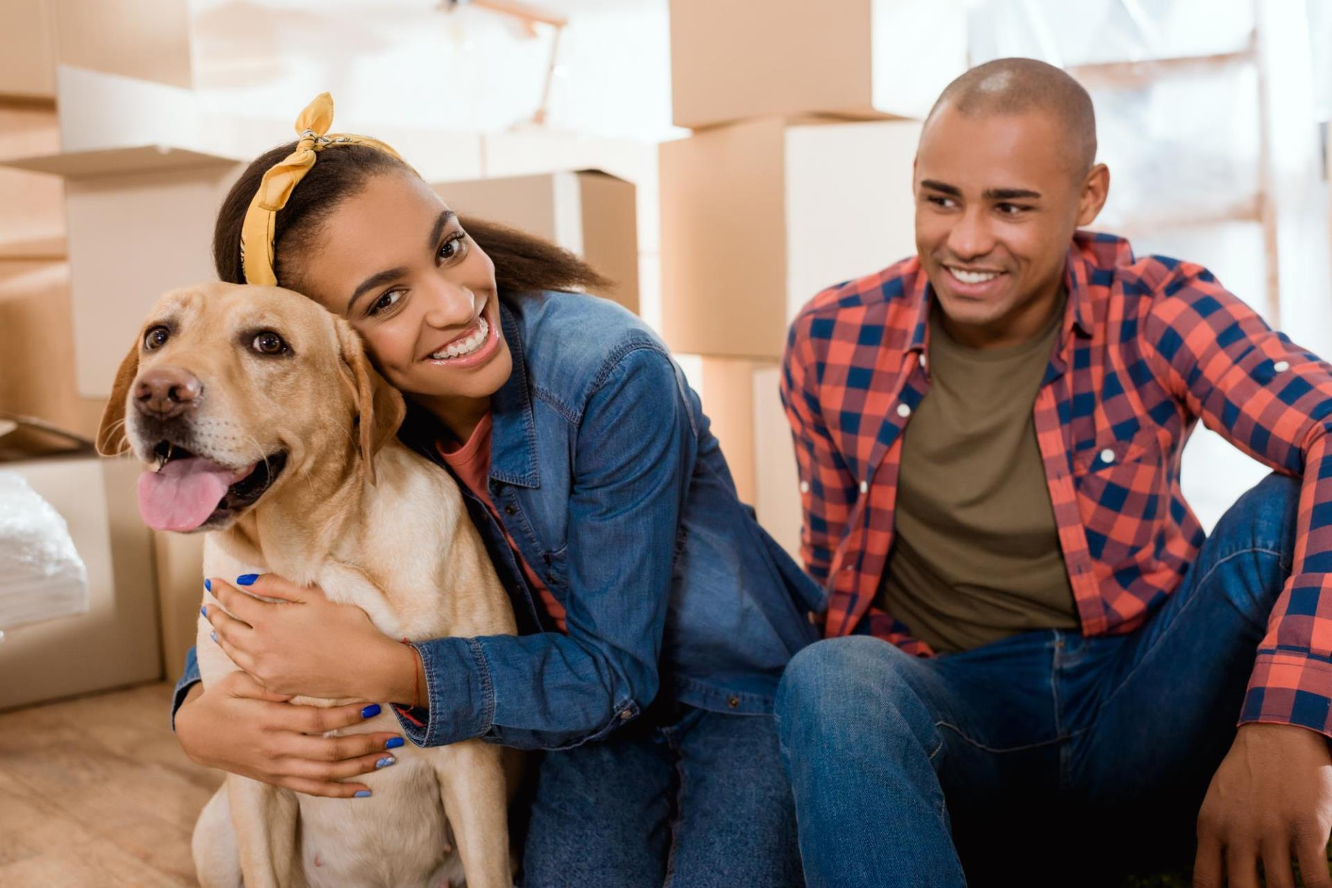 Man, women and dog with moving boxes behind them